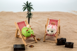 a piggy bank is located in a deck chair. symbolic photo for trav