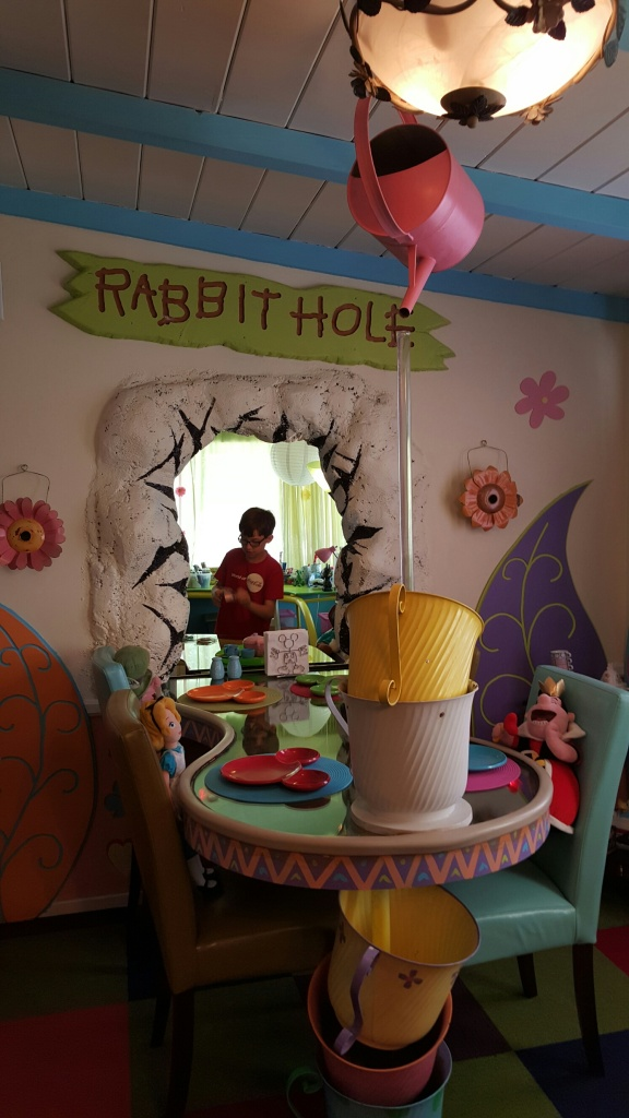 """The first thing that caught my attention was the large """"Rabbit Hole"""" in the wall and then my eyes drifted to the Alice in Wonderland tea party set up. The large tube above the cups is actually a fountain. So fun!"""